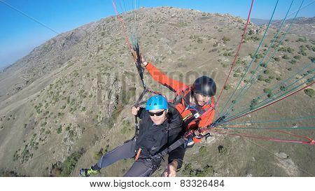 tourist paragliding above mountain range