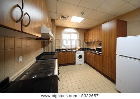 Kitchen With Brown Cupboards, Washingmachine, Cooker And Fridge