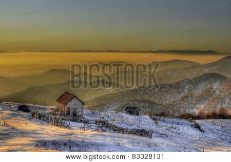Fog over mountain range at sunset