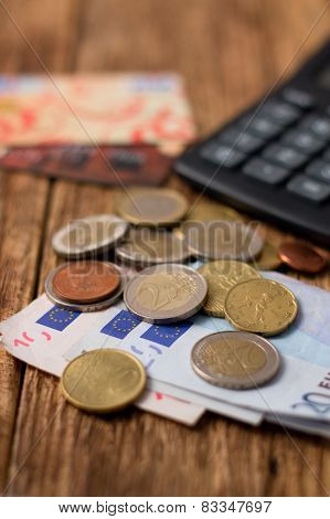 Euro Coins And Bills On Wooden Board