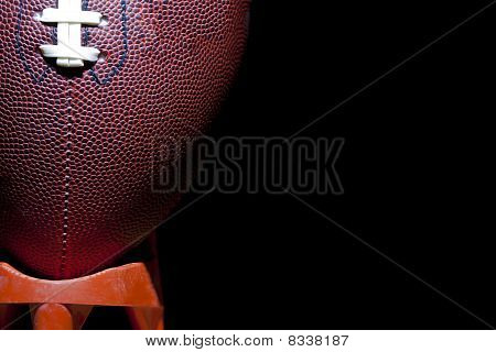 close up of an american football against a black background poster