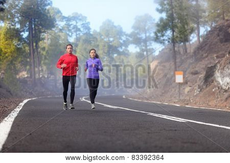 People running - athlete runners training jogging in cloudy and cold weather. Exercising runner couple working out living healthy lifestyle training for marathon together on mountain road.
