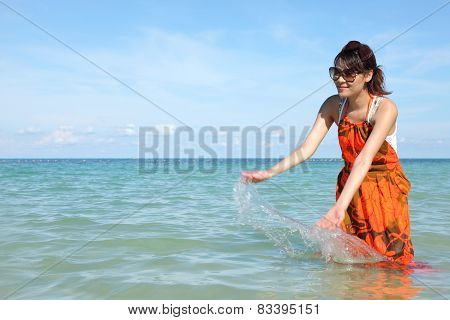 Beautiful young girl splashing the water in the sea
