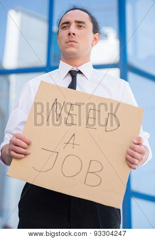 Man in suit holding sign in hands. Unemployed man looking for job. poster