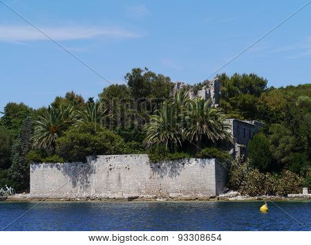 The castle of Ilovik with palm trees in Croatia