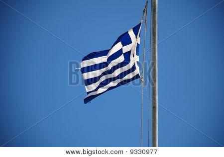 The Greek national flag flying at Emborio on the Greek island of Halki. poster