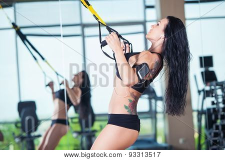attractive woman does crossfit push ups with trx fitness straps in the gym's studio
