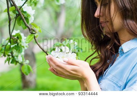 Young woman holding an apple flower
