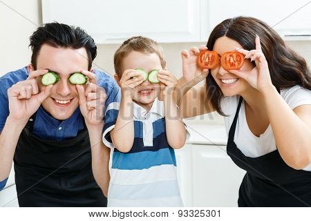 Funny family playing with food in kitchen