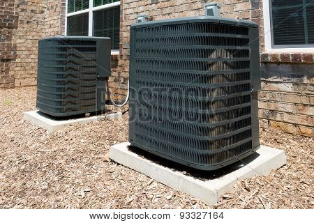 Two Air conditioner units attached to the residential building poster