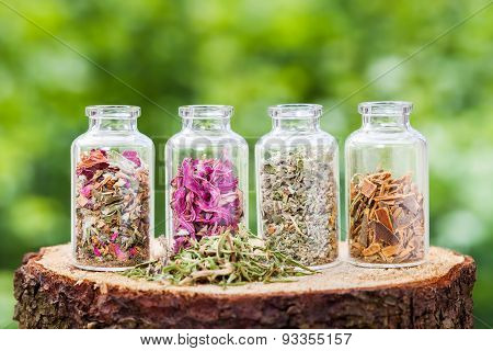 Glass Bottles With Healing Herbs On Wooden Stump On Green Background, Herbal Medicine.