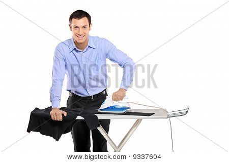 Happy Young Man Ironing His Clothes