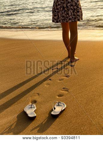 Woman Walking On Beach Into Ocean