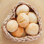 Brazilian snack cheese bread (pao de queijo) in wicker basket on wooden table. Selective focus poster