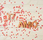 Ti Amo meaning I Love You in Italian written with the block letters covered with red heart shaped confetti over the wooden background poster