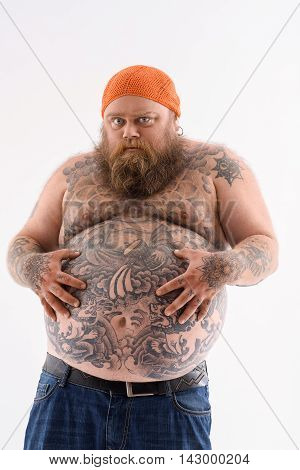 I am very hungry. Fat man is touching his naked belly with tattoo. He is standing and looking forward with desire. Isolated poster