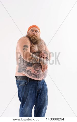 Scared fat man is looking at camera with fear. He is standing and posing with naked belly. Isolated