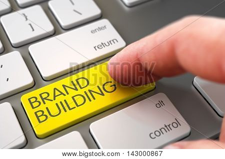 Business Concept - Male Finger Pointing Yellow Brand Building Key on Metallic Keyboard. 3D Illustration.