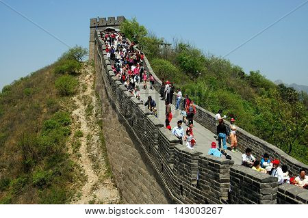 Badaling China - May 1 2005: Throngs of visitors \walking along the crenelated ramparts of the Great Wall of China