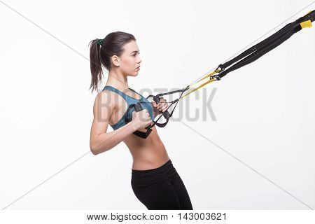 Upper body excercise concept. Beautiful lady training with suspension trainer sling or suspension straps isolated on white background in studio.