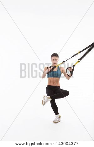 Upper body excercise concept. Picture of beautiful fitness trainer or coach showing her strong body with muscles. Pretty lady training with suspension trainer sling isolated on white background.