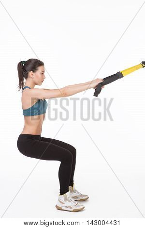 Beautiful woman training with suspension trainer sling or suspension straps in studio. Profile of lady exercising her body with muscles.