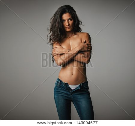Topless Woman Standing In Grey Room Stares Ahead