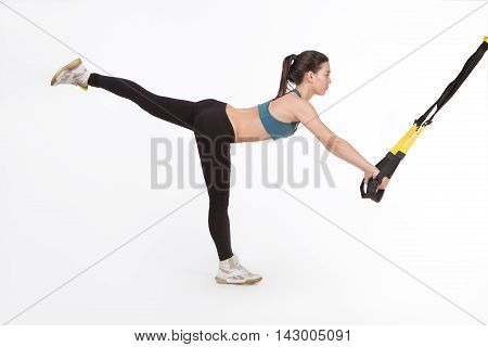 Picture of fitness lady training with suspension trainer sling or suspension straps in studio. Attractive young woman exercising with modern sports equipment.