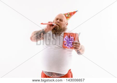 Cheerful fat man is celebrating his birthday. He is blowing into toy with joy. Man is standing and holding present box. Isolated