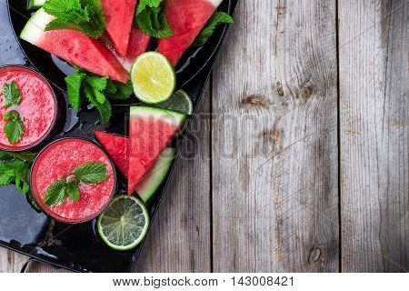 Still life, food and drink, diet concept. Organic fresh watermelon slices with mint lime and drink smoothie on a grunge black table. Selective focus, top view flat copy space