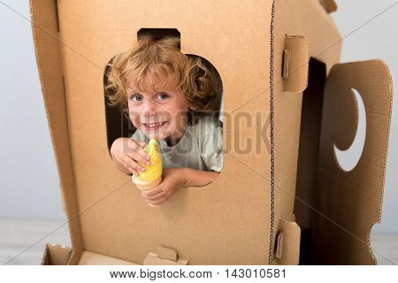 Departure time. Cute adorable boy sitting in the carton rocket and looking through the window while holding ice cream of plastic