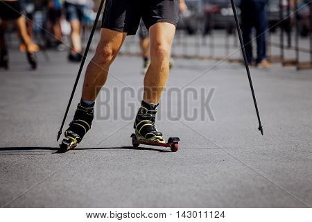 legs men racer in ski-roller rides on asphalt