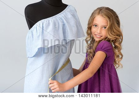 I adore this job. Fascinating little girl taking waist measurement with a tape and looking at the camera on the grey background