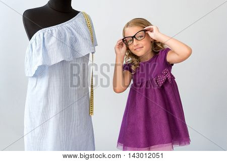 To see you better. Enchanting little girl putting on glasses and looking at the camera while standing near a mannequin with a dress on it poster