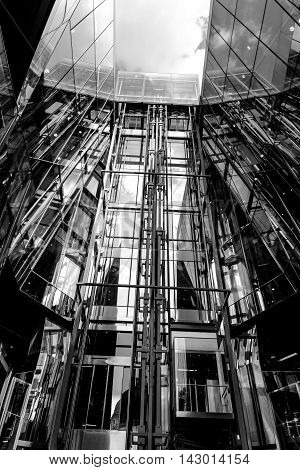 Grayscale low angle view of glass elevators moving up in down in towering atrium of commercial or residential building