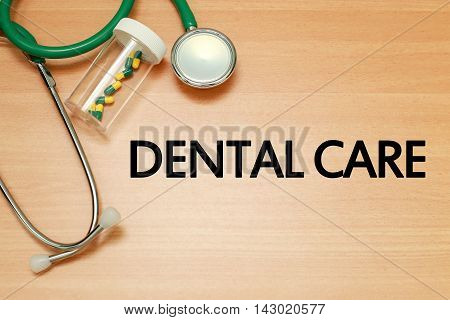 Medical concept - Stethoscope and pills on wood with Dental care word