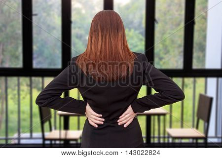 Woman lower back painful injury. Businesswoman backache and injury in office - office syndrome concept