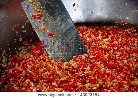 Red chili peppers chopped up using a cleaver within a metal bowl in Xitang town located in Zhejiang province China.