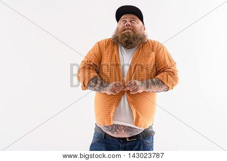 Fat man is trying to button his shirt on big belly. He is standing and looking up with efforts. Isolated and copy space in left side