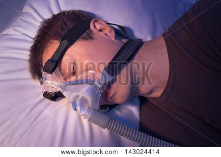 Middle age asian man with sleep apnea sleeping wering CPAP heargear connecting to air tube with night color effect