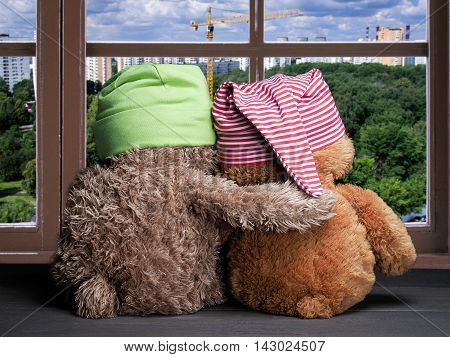 Two friends looking out the window. Panorama of the city. Construction crane. Toys colorful hats bear cubs. Embrace the window. Concept - friendship and support.