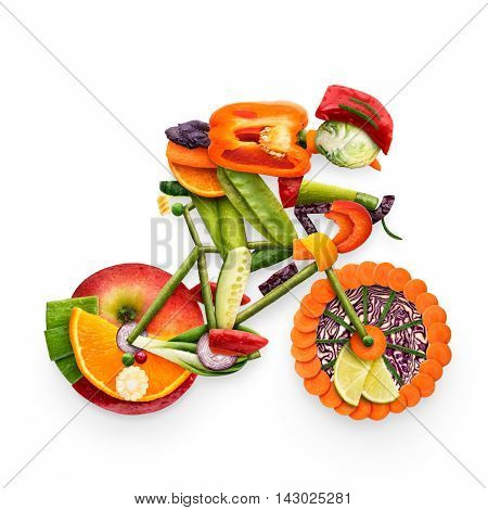 Healthy food concept of a cyclist riding a bike made of fresh vegetables and fruits isolated on white.