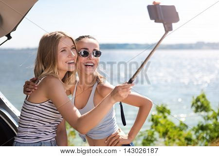 Just smile. Cheerful delighted friends making selfies and standing near car while resting on the seaside