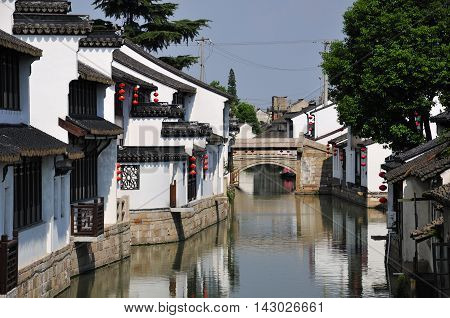 White tradional chinese buildings lining a water canal in Luzhi town in Jiangsu province china.