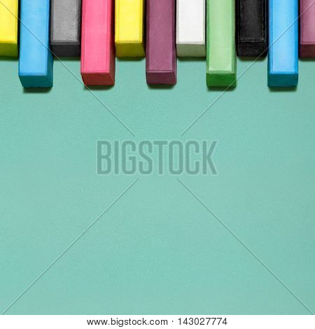 Creative still life of multicolored chalks arranged in a row like piano keys.