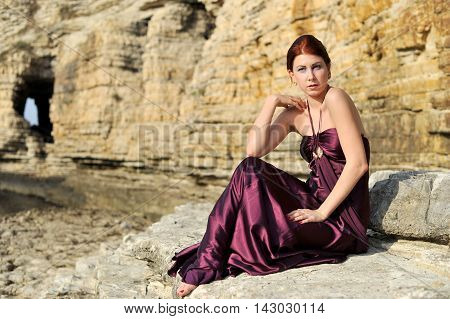 beautiful young fashion women posing on the nature with claret red dress