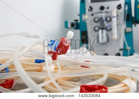 Bloodline tubes with hemodialysis machine in the background. Health care blood purification kidney failure transplantation medical equipment concept with copy space.