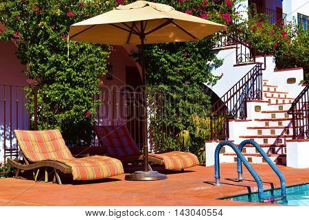 Lounge chairs with an umbrella beside a pool taken at a courtyard in a Spanish style Hacienda Villa