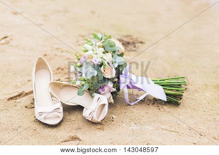 Beautiful boho rustic composition with a bridal bouquet and wedding shoes standing on a beach sand