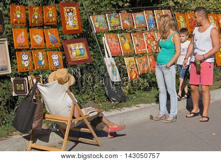 Kiev Ukraine - September 20 2015: Passers-by examine the work of the artist sold the painting in the street Andrew's Descent